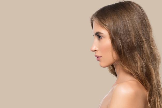 Portret profil twarz uroda kobiety. zdrowa, piękna skóra kobieta na brązowym tle