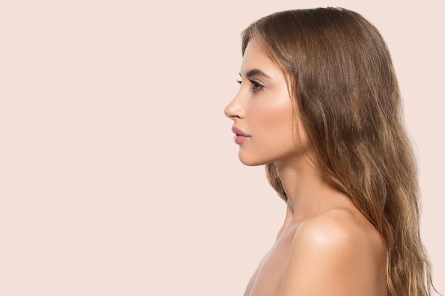 Portret profil twarz uroda kobiety. zdrowa, piękna skóra kobieta na różowym tle