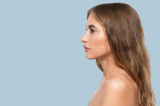Portret profil twarz uroda kobiety. zdrowa, piękna skóra kobiety na niebieskim tle