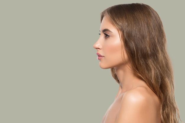 Portret profil twarz uroda kobiety. zdrowa, piękna skóra kobiety na zielonym tle