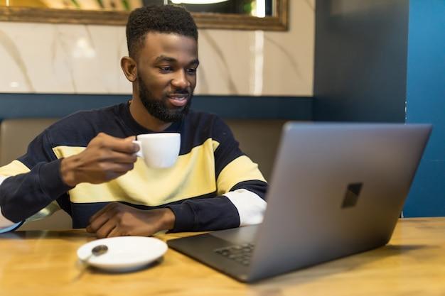 Portret profilowy młodego afrykańskiego kierownika sklepu internetowego, pijącego kawę podczas pracy w kawiarni