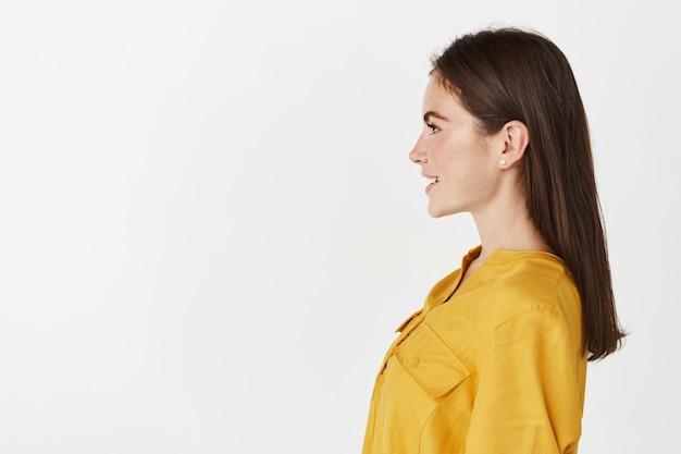 Portret profilowy młodej pewnej siebie kobiety stojącej na białej ścianie, patrzącej w lewo i uśmiechniętej, ubranej w żółtą bluzkę