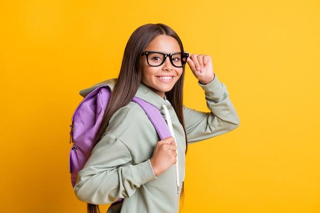 Portret profilowy osoby szkolnej ramię dotykać okularów nosić plecak na białym tle na żółtym tle