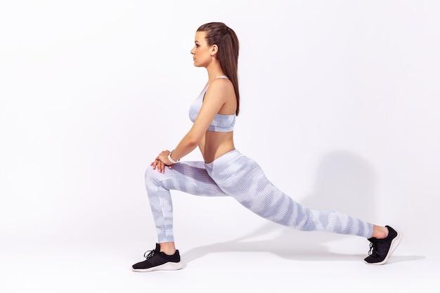 Portret profilowy pełnej długości wysportowana kobieta w białej odzieży sportowej robi ćwiczenia sportowe dolnej części ciała