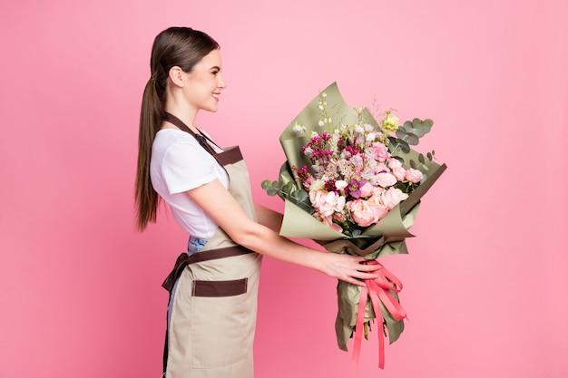 Portret profilowy słodkiej dziewczyny noszącej fartuch przedstawiający bukiet organicznych kwiatów