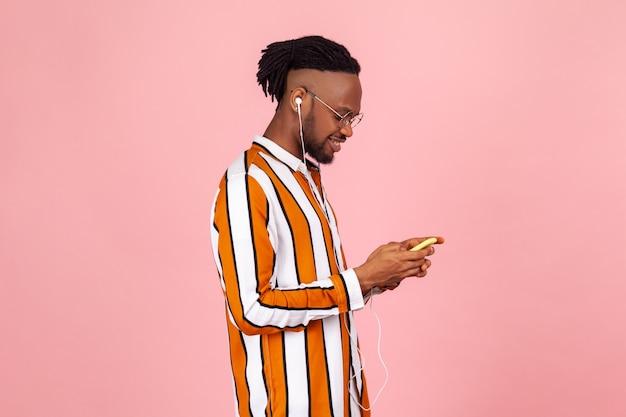 Portret profilowy stylowy afro-amerykański mężczyzna rozmawiający na smartfonie i słuchający muzyki