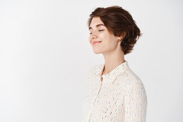 Portret profilowy szczerej pięknej kobiety zamyka oczy i uśmiech, odwraca twarz w lewo, pustą przestrzeń, obrazuje lub marzy, stojąc romantycznie na białej ścianie
