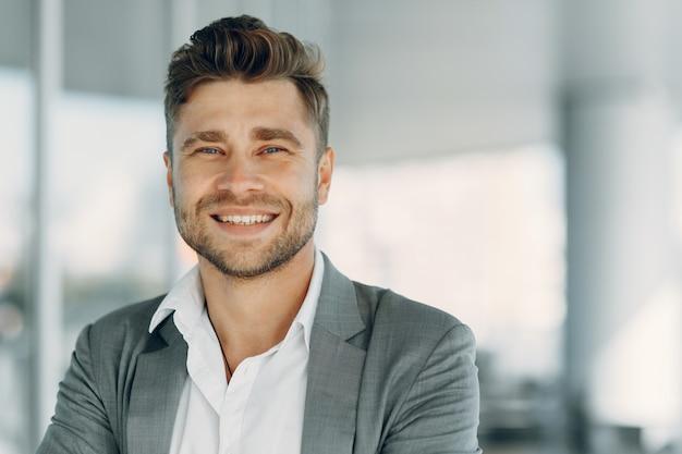 Portret profilowy uśmiechnięty i pewny siebie dojrzały biznesmen ubrany w garnitur młody mężczyzna