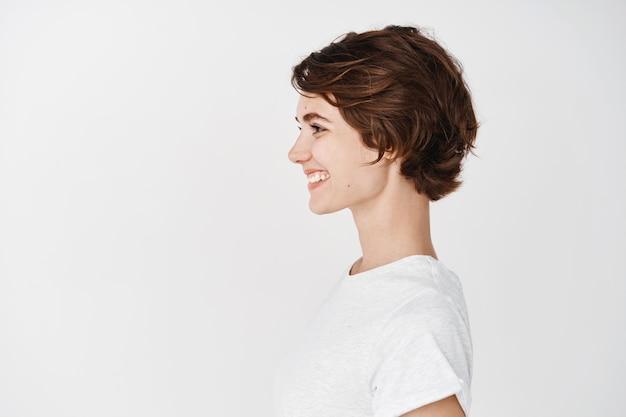 Portret profilowy zdrowej naturalnej kobiety z krótką fryzurą, uśmiechniętej i patrzącej w lewo na pustą przestrzeń, stojącej w koszulce na białej ścianie
