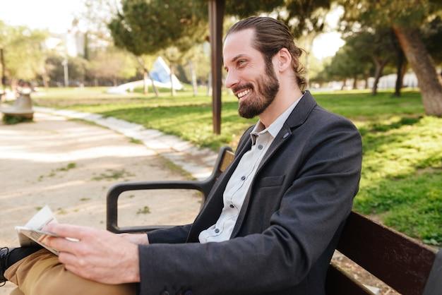Portret profilu szczęśliwy biznesmen w garniturze uśmiechnięty, siedząc na ławce w parku miejskim i czytając gazetę