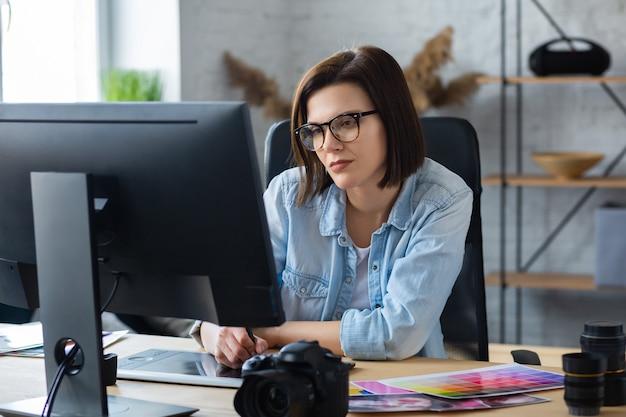 Portret projektanta graficznego pracującego w biurze z laptopem, monitorem, tabletem do rysowania graficznego i paletą kolorów. retuszowanie obrazów w specjalnym programie. miejsce pracy retuszera w studio fotograficznym. agencja kreatywna.
