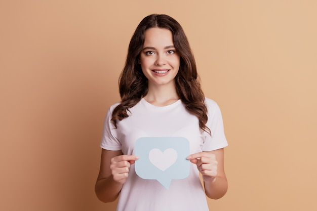 Portret promotora wesołej dziewczyny ręce trzymają ikonę serca powiadomienia odizolowaną na beżowym tle