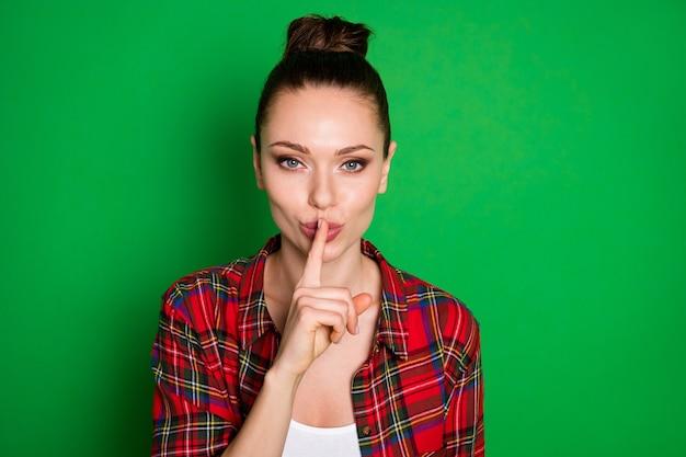 Portret przebiegłej chytrej dziewczyny planu zapytaj jej przyjaciela, aby nie mów nikomu tabu informacje umieścić palec wskazujący usta nosić dobrze wyglądające ubrania izolowane nad połyskiem kolor tła