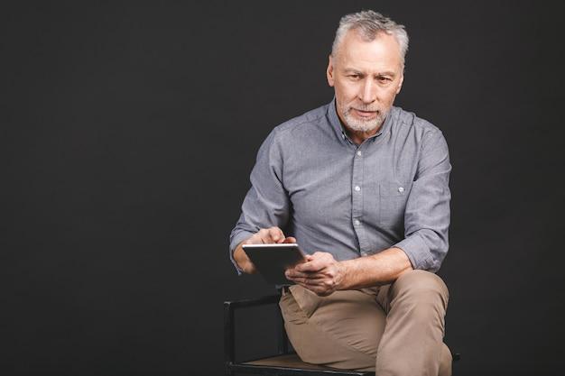 Portret przechodzić na emeryturę starszego mężczyzna trzyma w jego ręce cyfrową pastylkę podczas gdy siedzący, trzymający szkła.