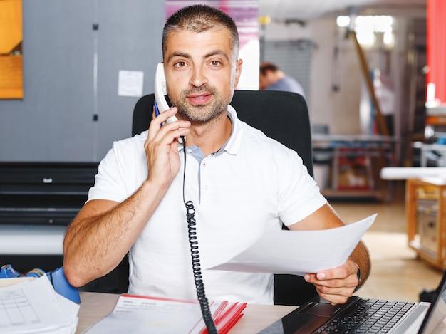 Portret przedsiębiorcy odnoszącego sukcesy biznesmena pracującego w zajętym biurze