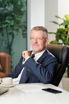 Portret przedsiębiorcy w średnim wieku siedzi przy biurku z umową i filiżankę kawy przed nim