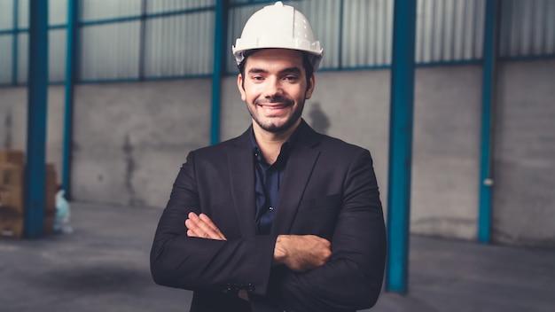 Portret przekonany kierownik fabryki w garniturze i kasku ochronnym