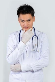 Portret przekonany młody lekarz na białej ścianie.