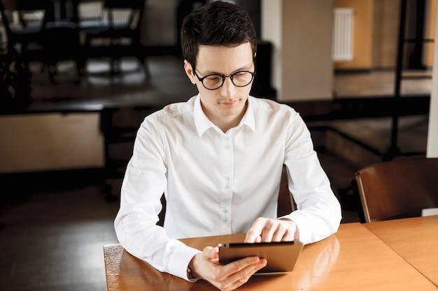 Portret przekonany, młody menedżer siedzi w kawiarni pracującej na tablecie ubrany w okulary.