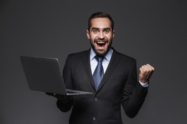Portret przekonany przystojny biznesmen ubrany w garnitur izolowanych, trzymając laptopa, świętuje sukces