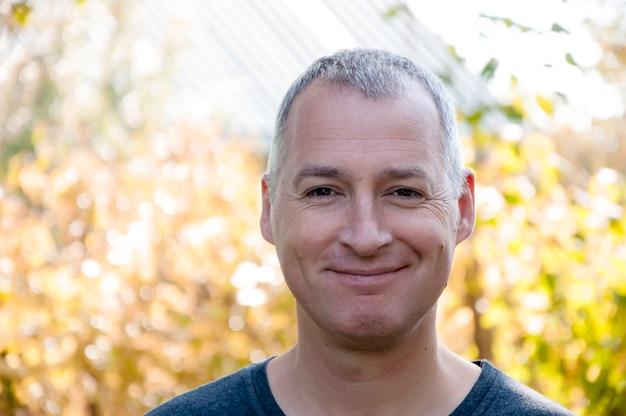 Portret przekonany, przystojny, siwowłosy mężczyzna w parku