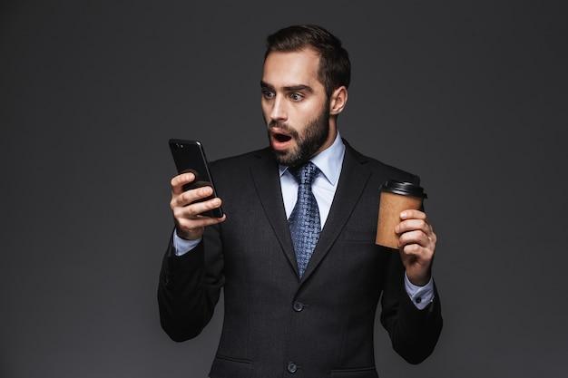 Portret przekonany, zszokowany przystojny biznesmen ubrany w garnitur na białym tle, trzymając kubek na wynos, przy użyciu telefonu komórkowego