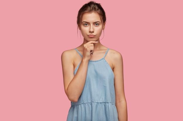Portret przemyślanej dziewczyny poważne trzyma brodę, patrzy z zdenerwowanym wyrazem twarzy bezpośrednio w aparacie
