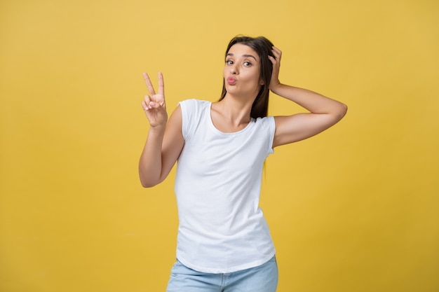 Portret przepięknej kobiety brunetka patrząc na kamery z uśmiechem i pokazując znak pokoju palcami na białym tle nad żółtym złotym tle.