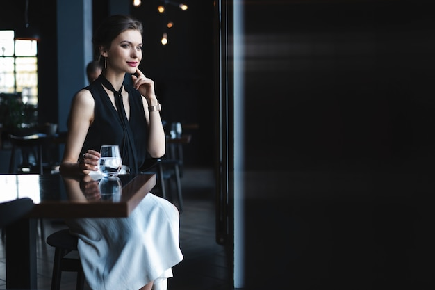 Portret przepięknej kobiety picia herbaty lub kawy i patrząc z uśmiechem przez okno kawiarni, ciesząc się jej wolnym czasem, miłą kobietą biznesową lunchem w nowoczesnej kawiarni podczas przerwy w pracy.