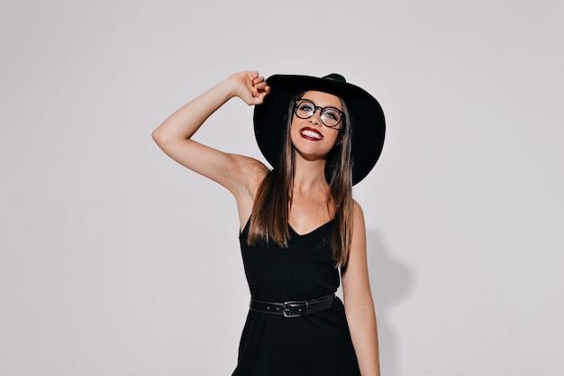 Portret przepięknej, niesamowitej czarodziejki brunetki, zakrywającej oczy czapką, gorącą sylwetką, ciałem. urocza kobieta w stroju czarownicy pozuje na odizolowanej ścianie
