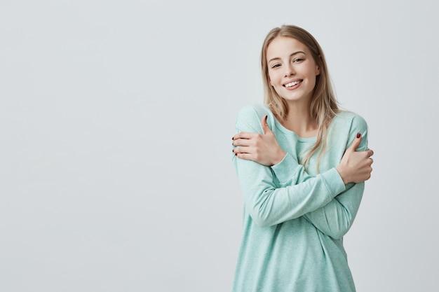Portret przepięknej pozytywnej młodej kaukaskiej kobiety z uroczym uśmiechem i długimi blond włosami, cieszący się miękką tkaniną jej nowego jasnoniebieskiego bluzki pozującej do szarej ściany