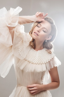 Portret przepięknej zmysłowej damy w białej puszystej sukience z kołnierzykiem ozdobionym perłowymi koralikami, trzymająca się za rękę z zamkniętymi oczami i oświetlonymi światłem w snach.