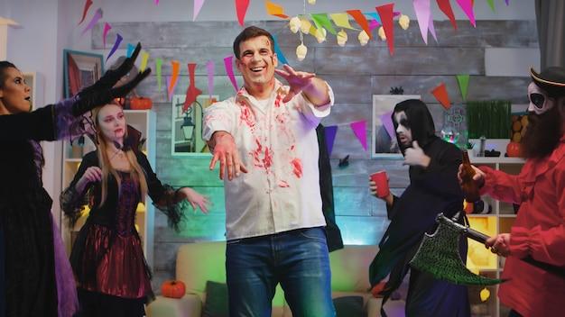 Portret przerażającego zombie tańczącego na imprezie z okazji halloween w pięknie urządzonym domu