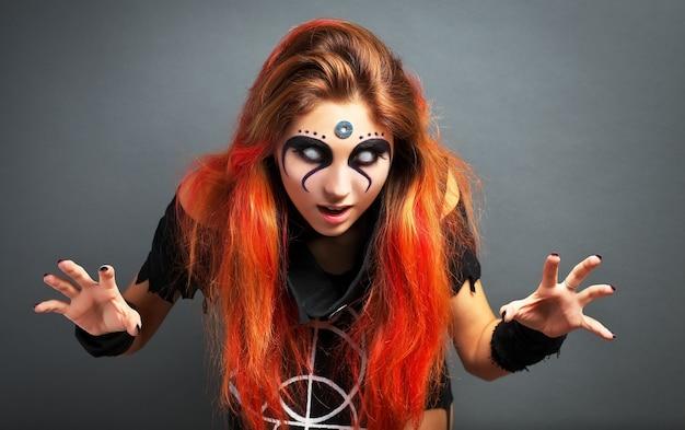Portret przerażającej młodej dziewczyny z białymi oczami na halloween na szarym tle