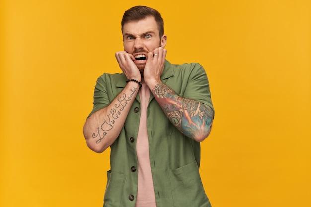 Portret przerażonego, dorosłego mężczyzny z brunetką i brodą. ubrana w zieloną kurtkę z krótkim rękawem. ma tatuaże. dotykanie twarzy ze strachu. pojedynczo na żółtej ścianie