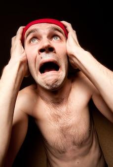 Portret przerażonego krzyczącego mężczyzny trzymającego głowę