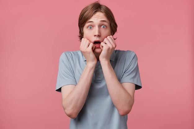 Portret przerażonego nastolatka w panice, zdenerwowany, podekscytowany, usta otwarte ze strachu, ubrany w koszulkę polo, trzyma dłoń na twarzy, czuje się przerażony, odizolowany na różowym tle z miejscem na kopię