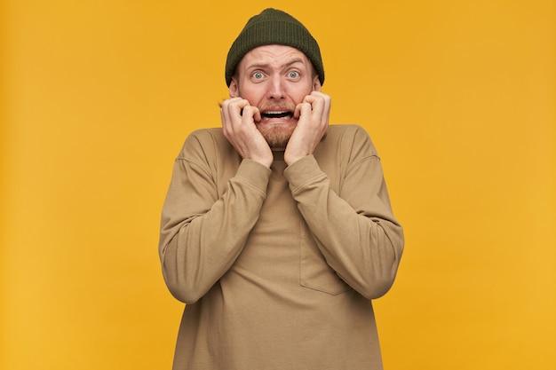 Portret przerażonego, przestraszonego mężczyzny z blond włosami i brodą. ubrana w zieloną czapkę i beżowy sweter. dotykając twarzy ze strachu. pojedynczo na żółtej ścianie