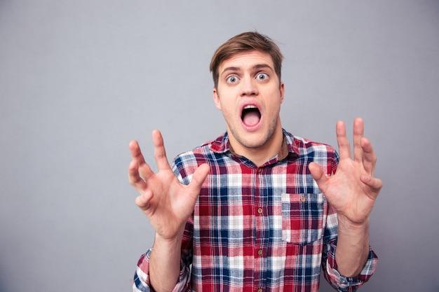 Portret przerażonego przestraszonego młodego mężczyzny w kraciastej koszuli krzyczącego z otwartymi ustami nad szarą ścianą