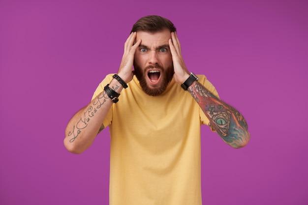 Portret przerażonego wytatuowanego brunetki z brodą, wyglądającego przerażająco z szeroko otwartymi ustami i trzymającego głowę z podniesionymi rękami, odizolowany na fioletowo