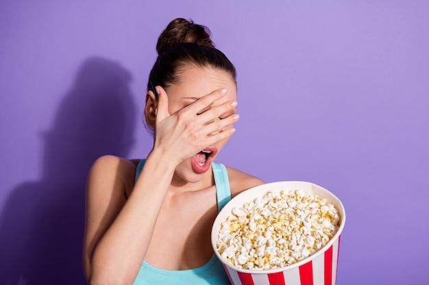 Portret przerażonej dziewczyny jedzącej kukurydzę oglądając thriller gatunkowy