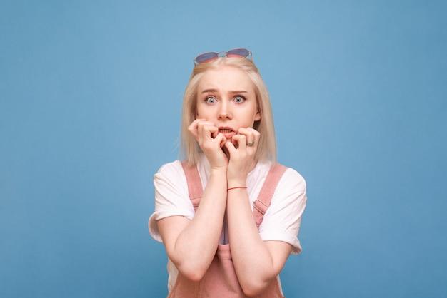 Portret przerażonej dziewczyny na niebieskim tle patrzy zszokowany w kamerę i gryzie palce. odosobniony