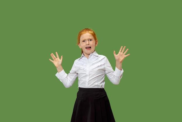 Portret przerażonej dziewczyny nastolatki. ona stoi na białym tle na modnym zielonym tle studio. portret kobiety w połowie długości. ludzkie emocje, koncepcja wyrazu twarzy.