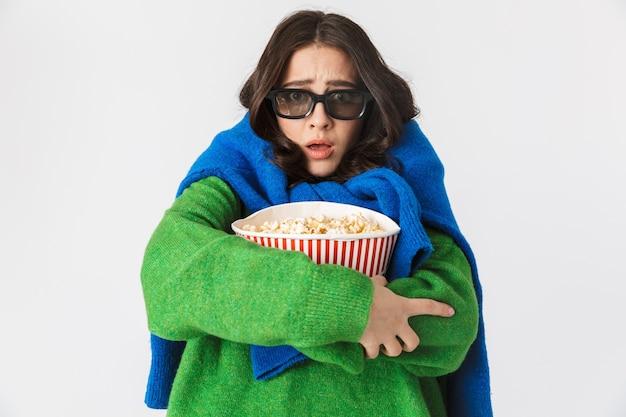 Portret przerażonej kobiety w ubranie ubrane w okulary 3d, jedzenie popcornu z wiadra, stojąc na białym tle