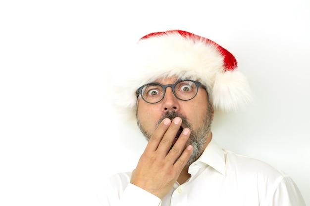 Portret przerażony lub zaskoczony mężczyzna w kapeluszu boże narodzenie na białym tle
