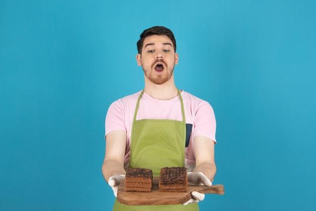 Portret przerażony młody człowiek na niebieskim gospodarstwa plastry ciasta.