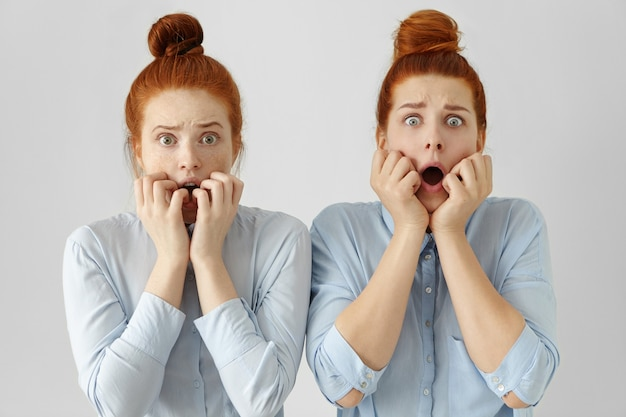 Portret przerażonych, przestraszonych młodych sióstr z rudymi włosami w kok