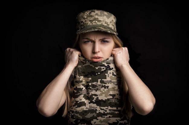 Portret przerażonych żołnierzy blond kobieta w strojach wojskowych na czarnym tle