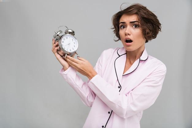 Portret przestraszona kobieta w piżamie trzyma budzika