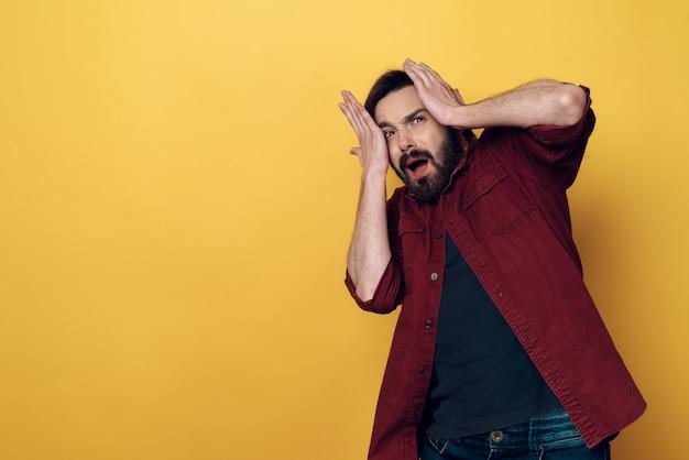Portret przestraszona krzycząca brodata mężczyzna chwyta głowa